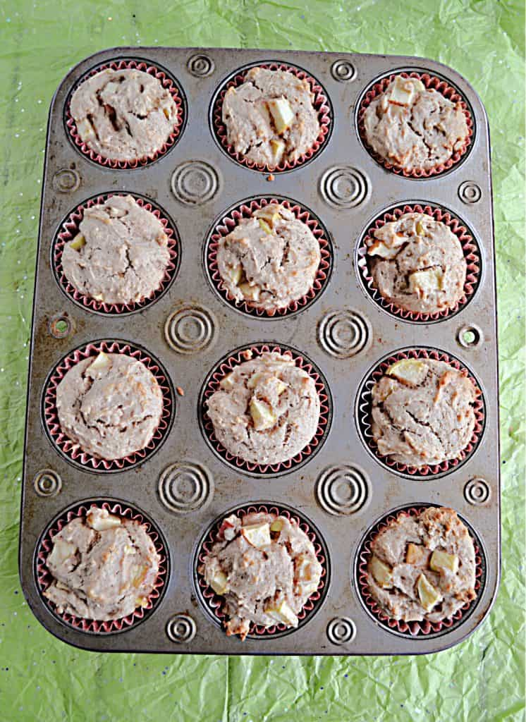 A muffin tin filled with apple cupcakes on a green background.