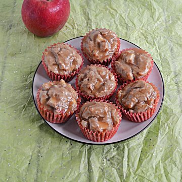 A plate with 7 apple cupcakes topped with brown sugar on it and an apple behind the plate.
