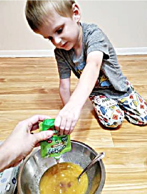 A picture of a 4 year old boy squeezing applesauce into cupcake batter.