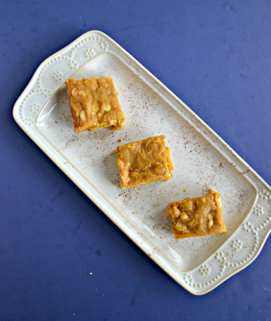A white platter sitting diagonally  with 3 blondies sitting on the platter on a blue background.