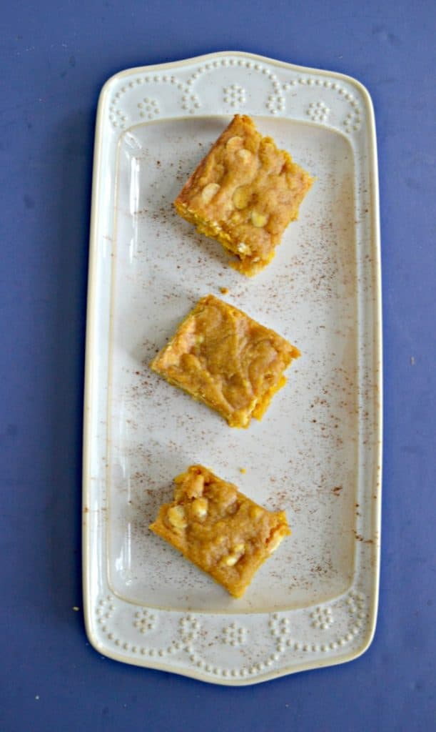 A white platter with 3 blondies sitting diagonally on the platter on a blue background.