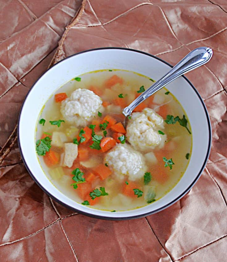 A bowl of Chicken Dumpling Soup with three large dumplings in it as well as a spoon.