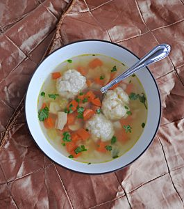 A bowl of Chicken and DUmpling Soup with three big dumplings, carrots, and celery, with a spoon in it.