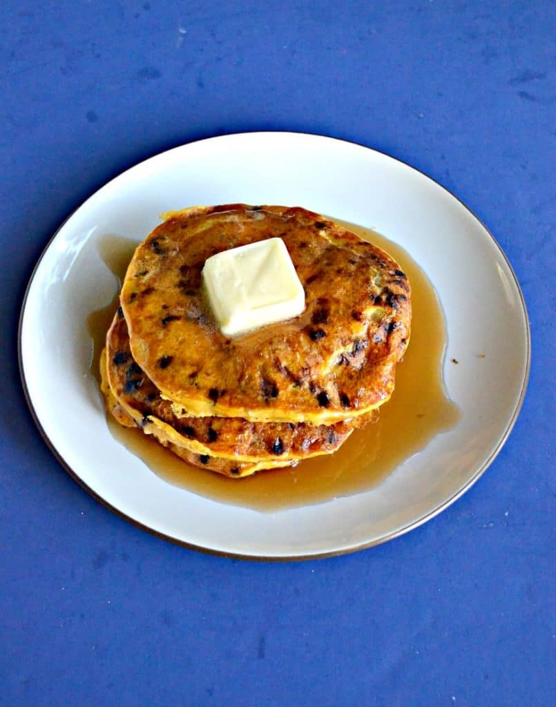 A white plate topped with a stack of three orange colored pumpkin pancakes studded with chocolate chips with a large pat of butter in the center and covered in syrup on a blue background.