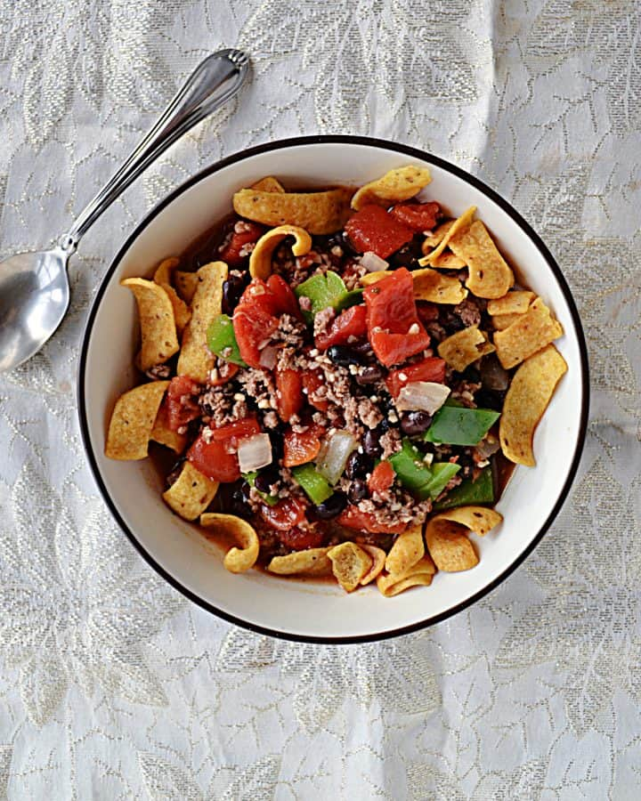 A bowl of Frito corn chips topped with a hearty chili with a spoon next to it.