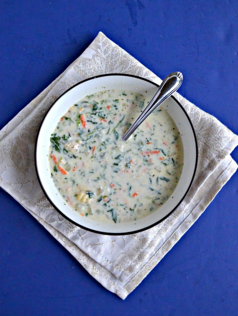 A bowl of creamy white soup dotted with carrots, spinach, and gnocchi with a spoon in it on a white napkin with a blue background.