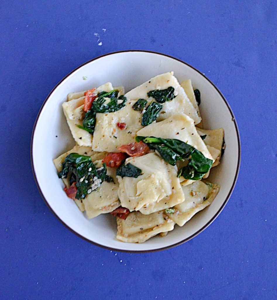 A bowl filled with ravioli, spinach, and bacon.