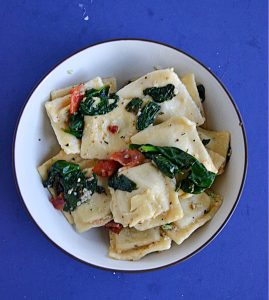 A close up view of a bowl of ravioli topped with spinach and bacon.