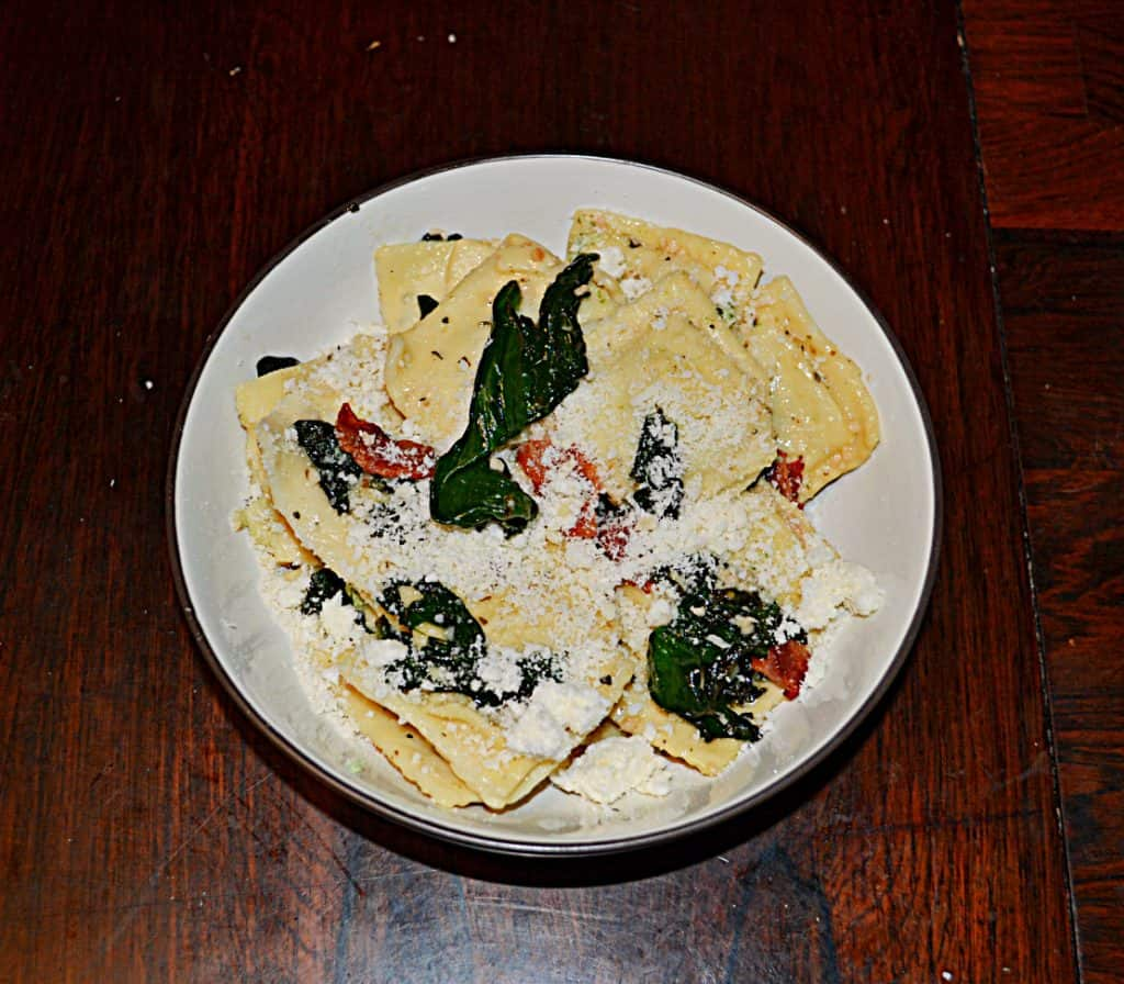 Ravioli Florentine in a bowl topped with spinach, bacon, and parmesan cheese.