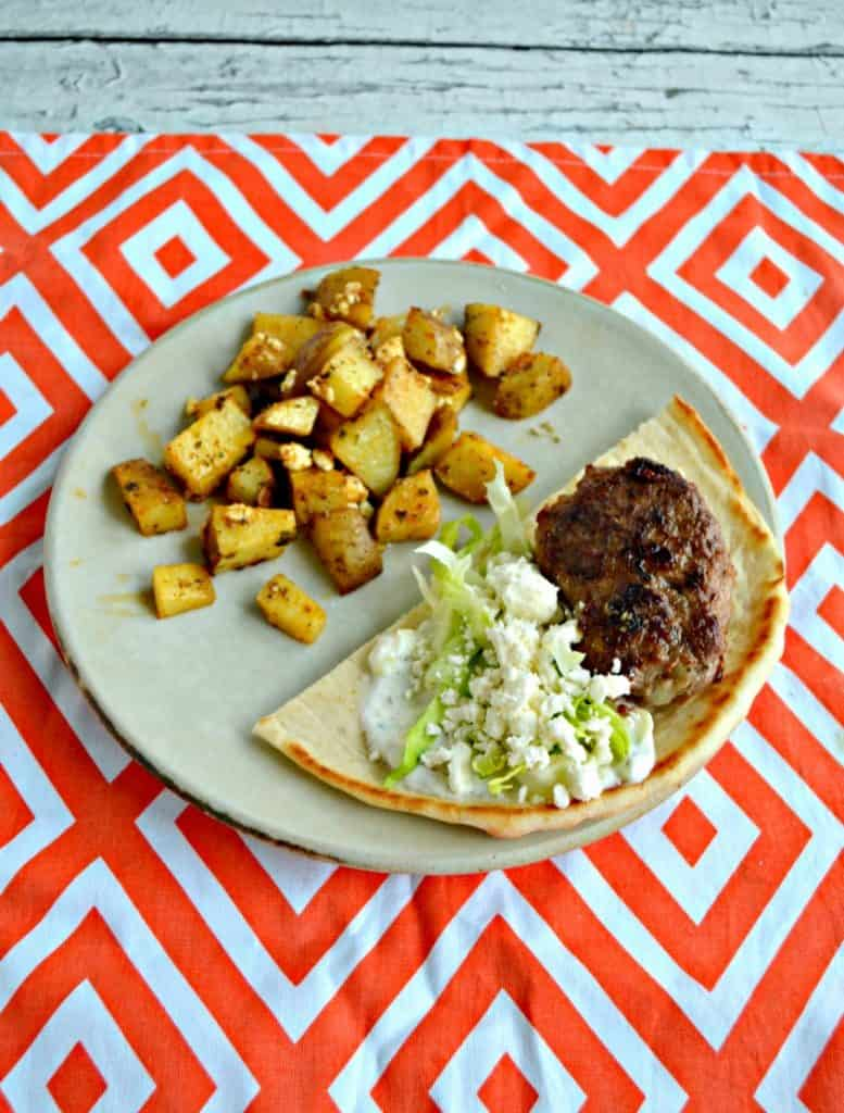 Lamb burger, feta, and lettuce in a pita with Greek potatoes all on a plate