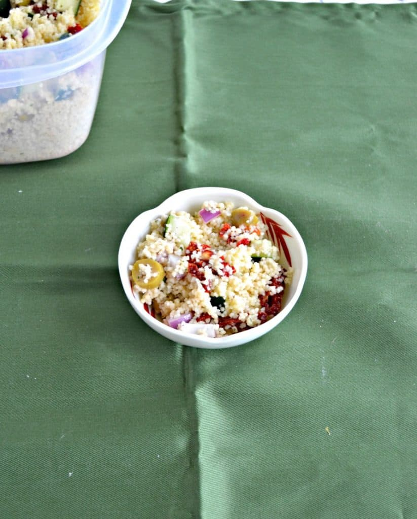 A small bowl of Greek Couscous salad with the container behind it