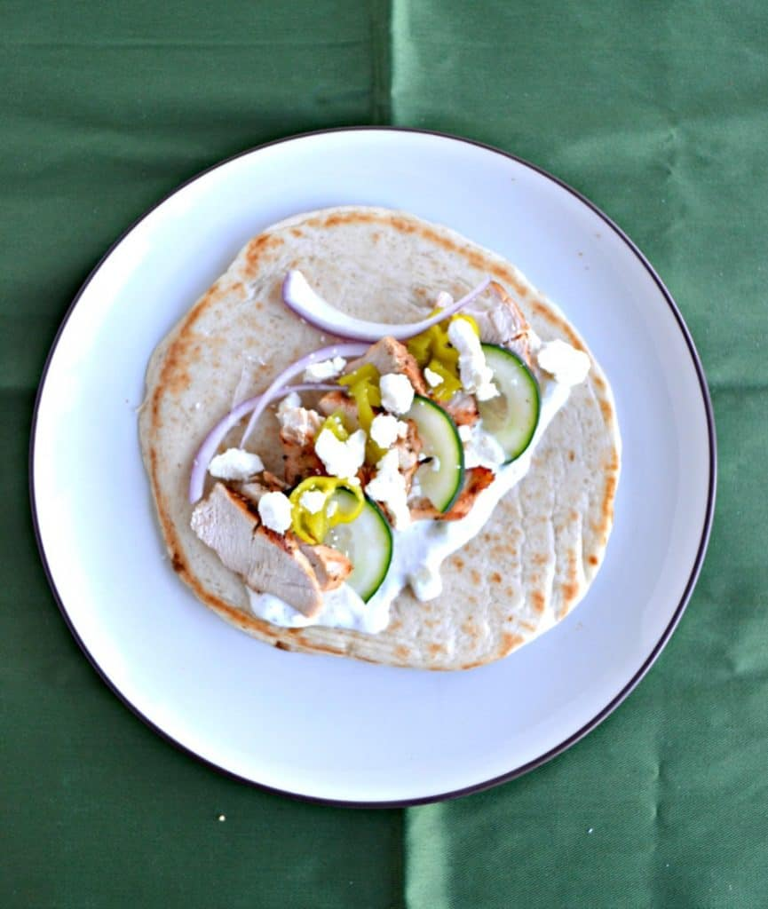 Pita bread topped with grilled chicken, cucumber, and red onions on a plate.