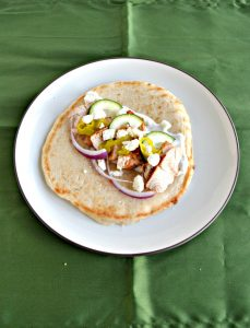 Pita bread on a plate topped with sliced chicken, red onions, feta, and cucumber slices.