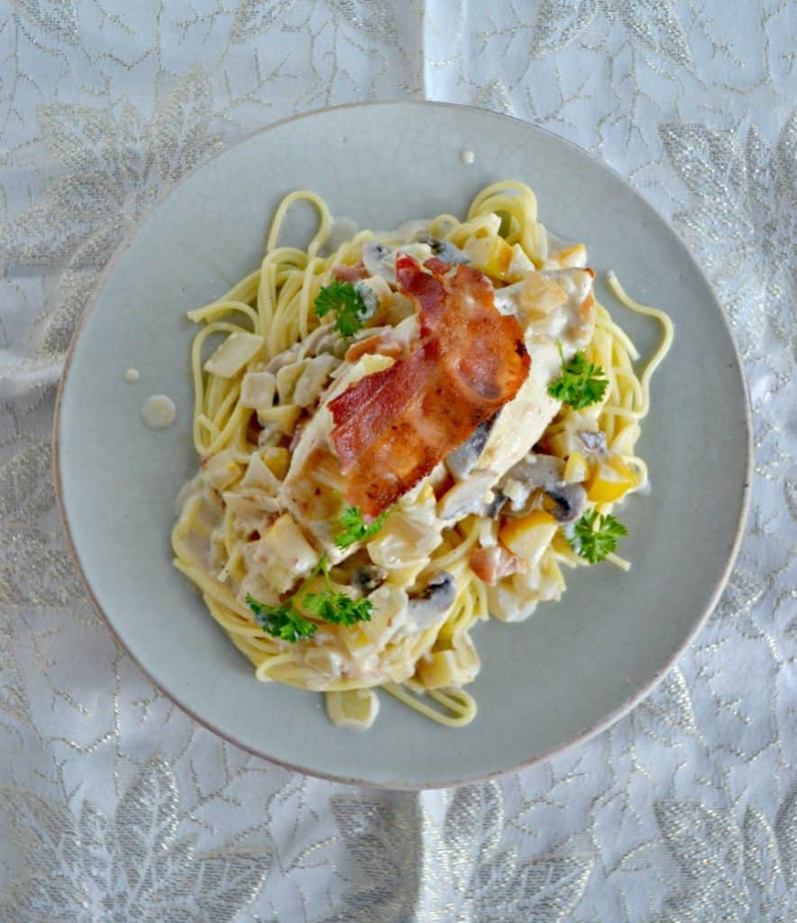 A plate piled high with spagehtti noodles, a creamy sauce, a large chicken breast topped with crispy bacon and fresh parsley on top.