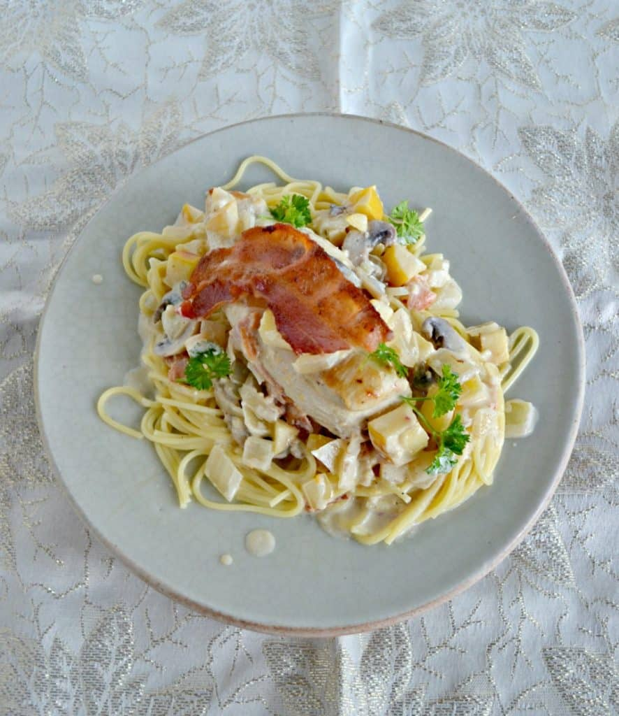 Side view of a plate piled high with spagehtti noodles, a creamy sauce, a large chicken breast topped with crispy bacon and fresh parsley on top.