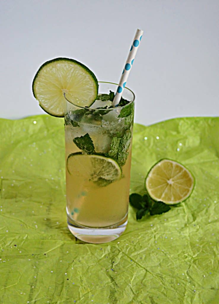 A tall glass with a mojito in it with lime slices and mint leaves floating in it and a straw sstuck in the glass and a half lime beside the glass.