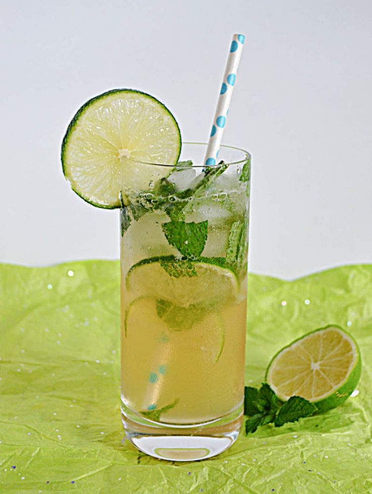 A glass of mojito with a lime slice on the rim and a straw stuck in it and a half lime on the side.