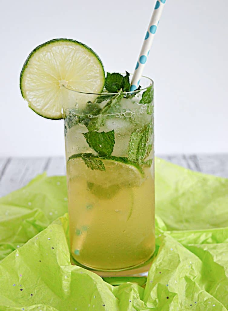 Close up of a glass of mojitos with limes and mint in the glass, a slice of lime on the rim, and a straw sticking out of it.