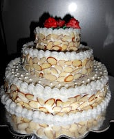 Triple Layer Cake decorated with sliced almonds and topped with Buttercream roses.
