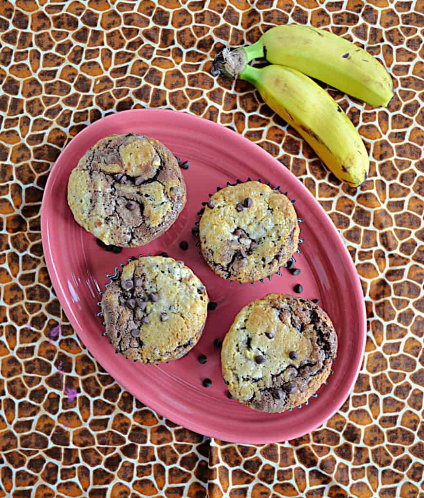 A pink platter topped with 4 banana chocolate chip muffins and two bananas on the side.