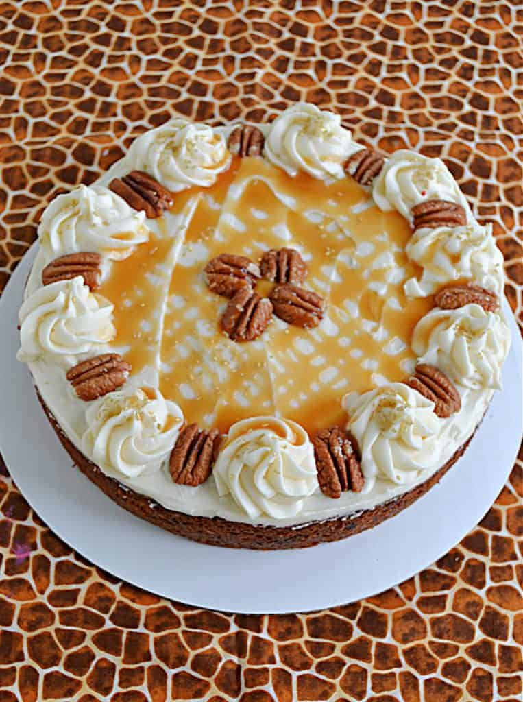 A butternut squash cake topped with frosting, caramel drizzle, and pecans.