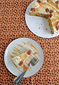 A slice of butternut squash cake topped with caramel frosting, a caramel drizzle, and pecans with two forks on the plate and the whole cake missing a slice in the corner.