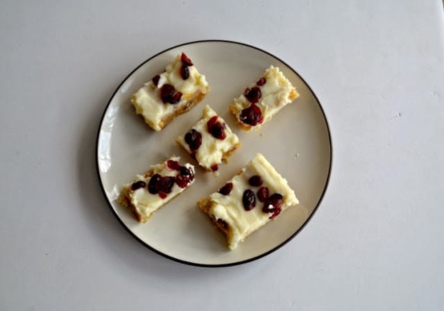 White Chocolate cookie bars topped with cream cheese frosting and cranberries