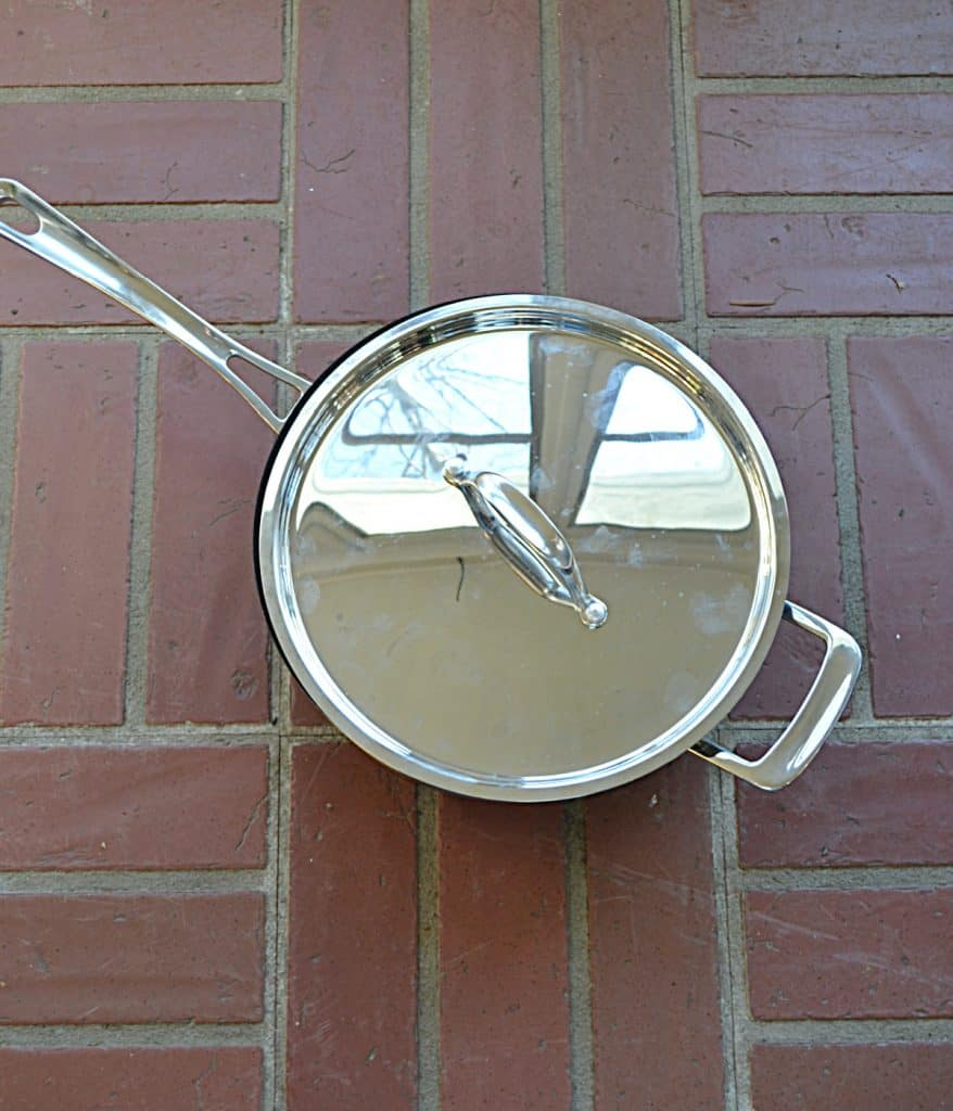 A large, silver skillet with a lid on it on top of a brick background.
