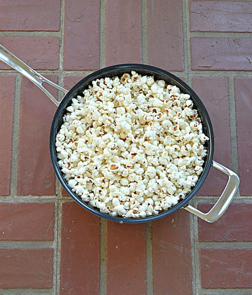 A large, silver skillet full of fluffy white popcorn on top of a brick background.