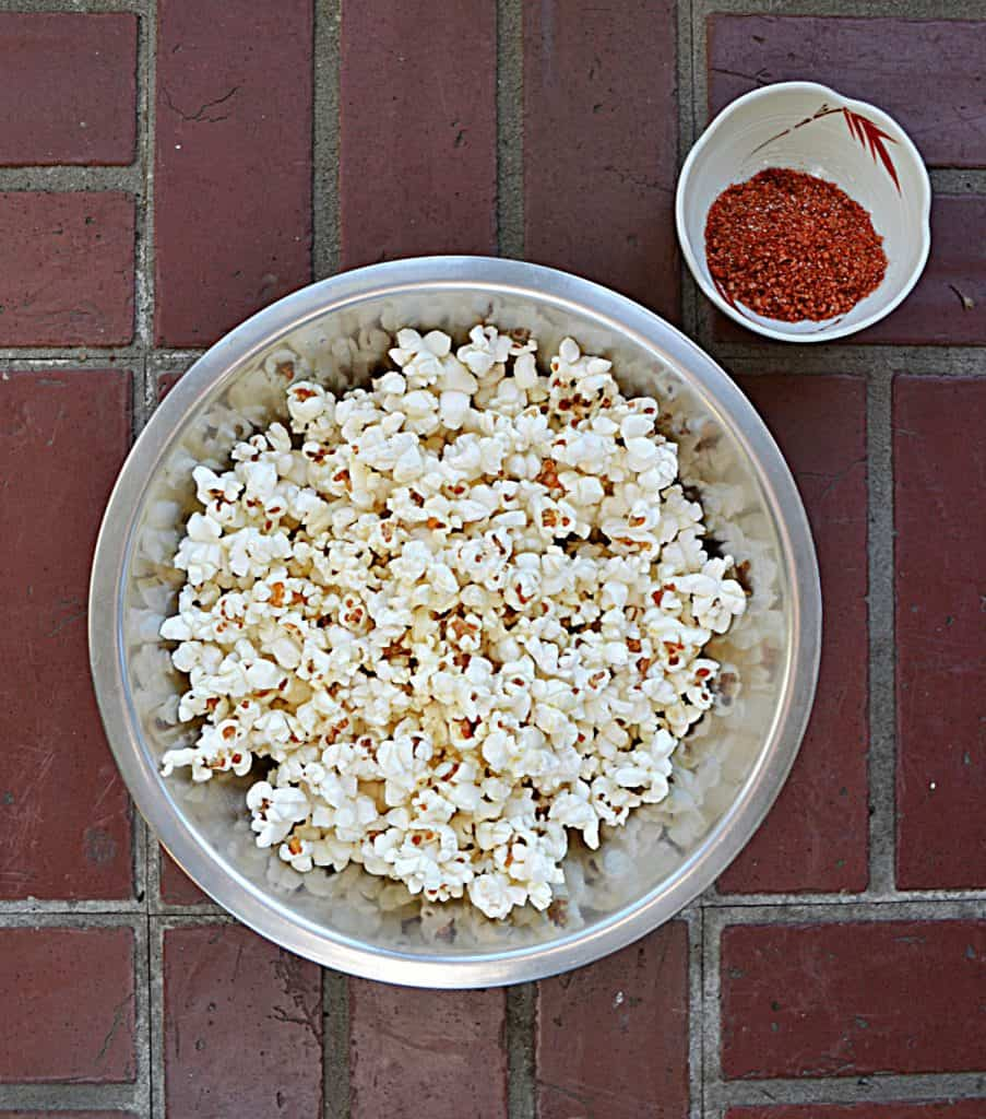 A bowl filled with fluffy white popcorn with a small bowl of red BBQ seasoning in the upper right hand corner all on a brick background.