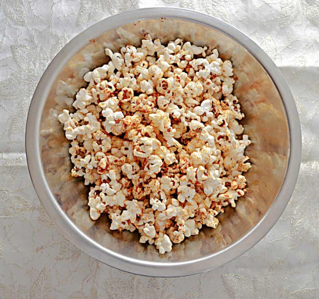 A silver bowl filled with popcorn sprinkled with red BBQ seasoning on a white background.