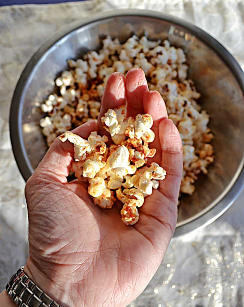 A silver bowl filled with popcorn sprinkled with red BBQ seasoning with a hand holding a handful of popcorn in the foreground on a white background.