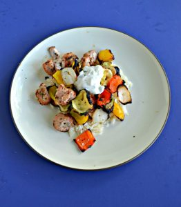 A plate piled high with white rice, grilled pork, and colorful veggies topped with a small spoonful of white Tzatziki sauce on a blue background.