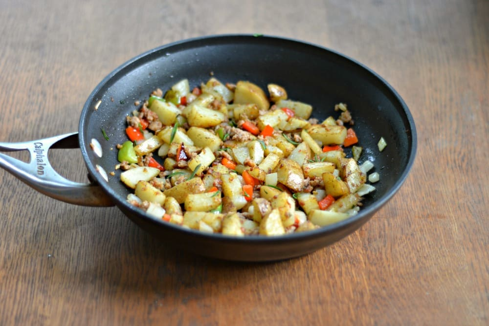 Spicy Skillet Breakfasst Potatoes contain bell peppers, onions, hot Italian sausage, and spices.