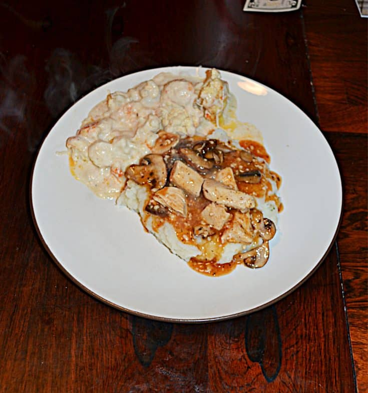 A plate with mashed potatoes topped with chicken, mushrooms, and onions in a white wine sauce and a side of cauliflower.