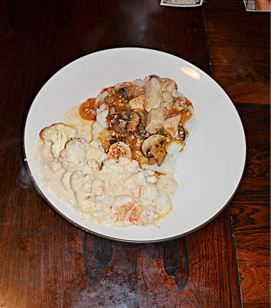 A plate with mashed potatoes topped with chicken, mushrooms, and onions in a white wine sauce and a side of creamy cauliflower.