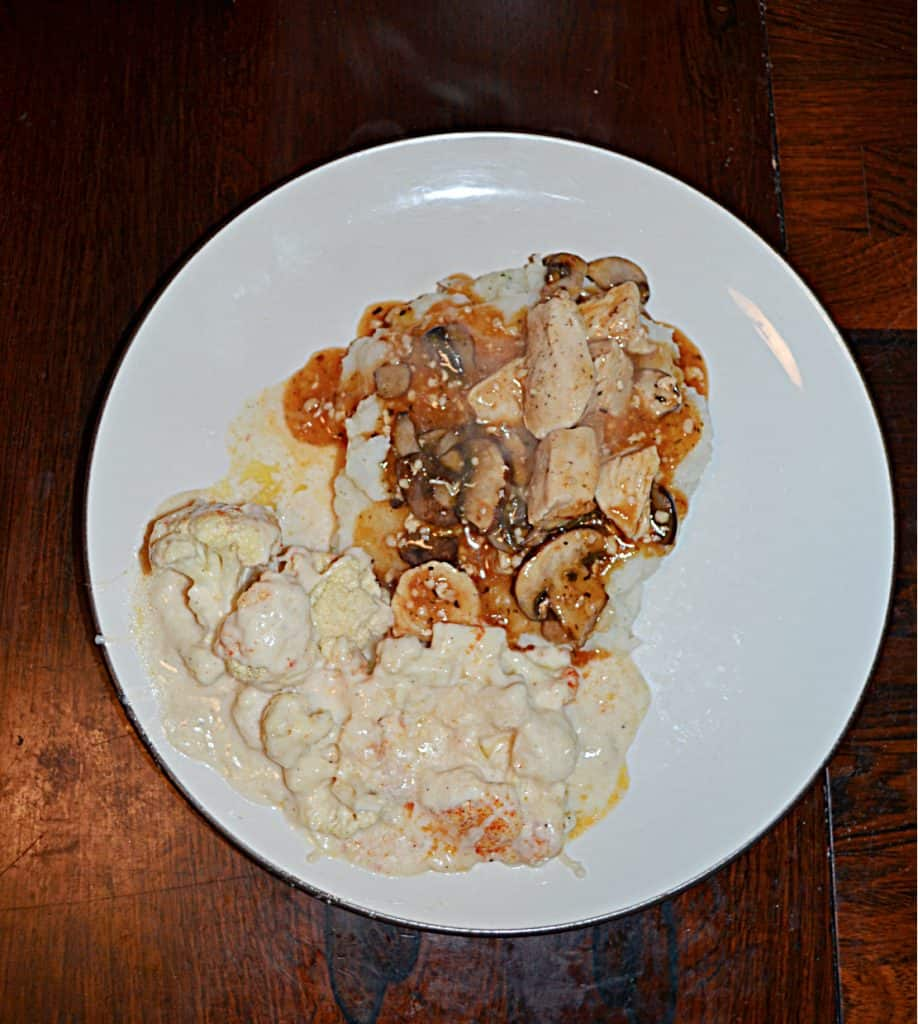 A top view of a plate with mashed potatoes topped with chicken, mushrooms, and onions in a white wine sauce and a side of cauliflower.