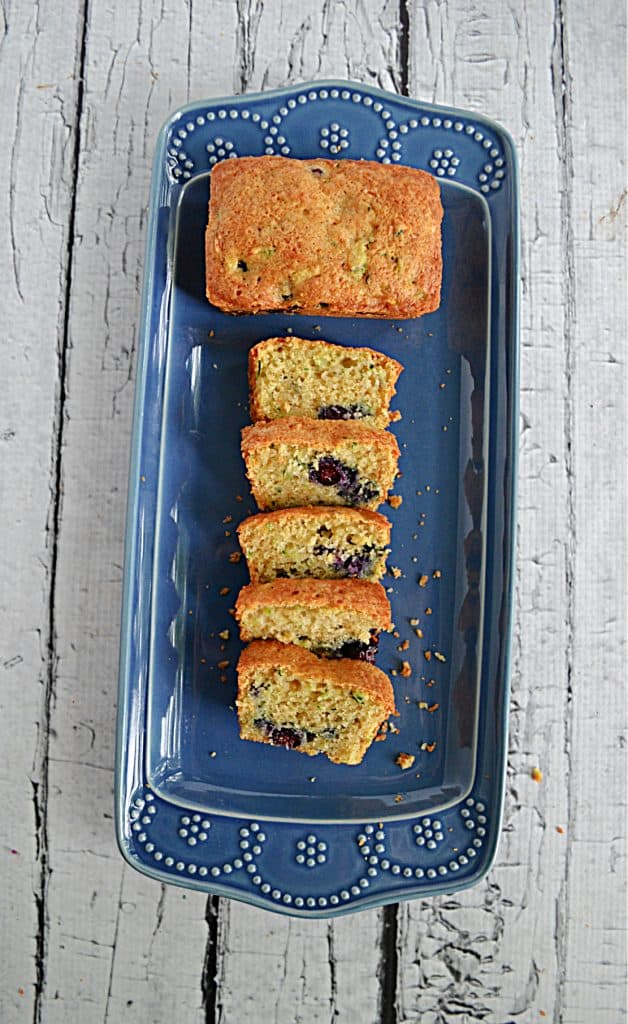 A platter with a mini loaf of blueberry zucchini bread on top with slices underneath.
