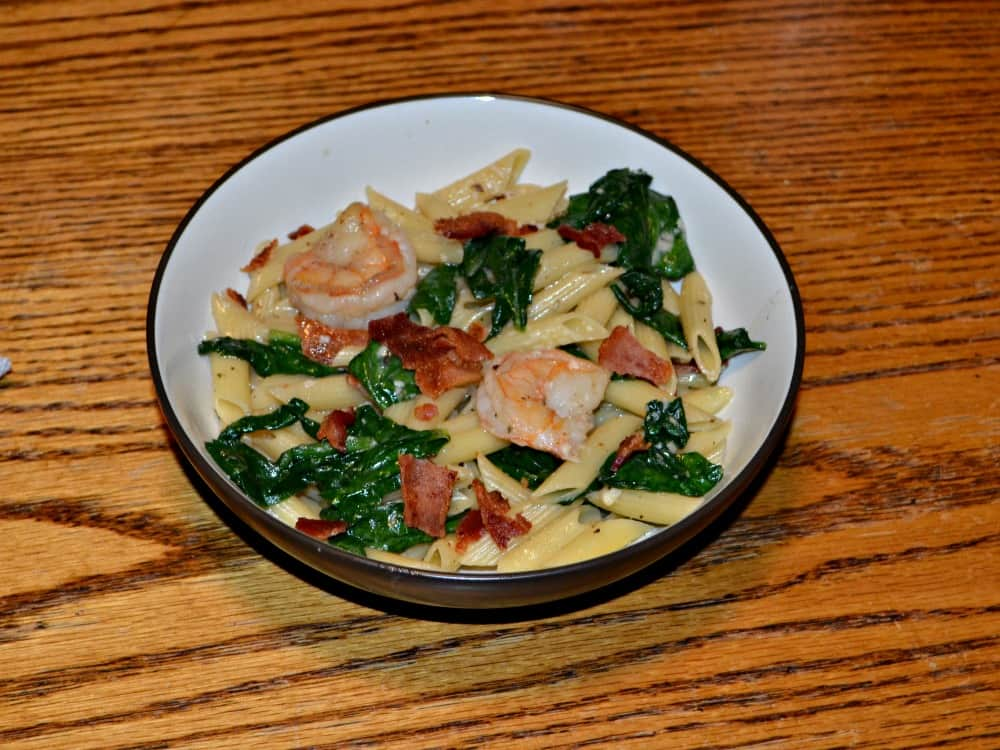 Shrimp and Bacon Pasta is tossed with spinach and a light sauce.