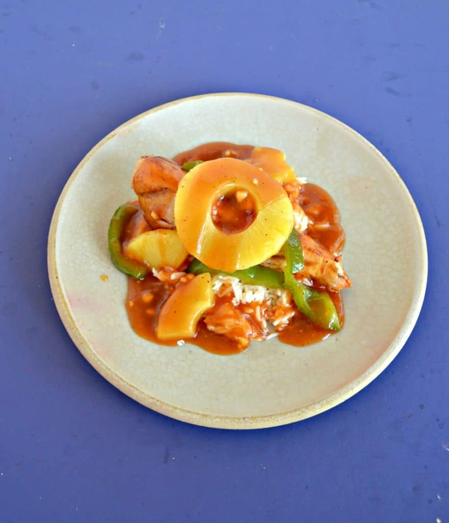 Angled view of a plate piled high with green peppers, chicken, pineapple, and red sweet and sour sauce with a pineapple ring on top on a blue background.