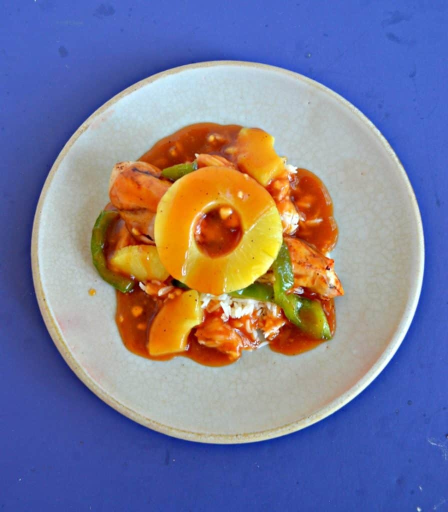 Top view of a plate piled high with green peppers, chicken, pineapple, and red sweet and sour sauce with a pineapple ring on top on a blue background.