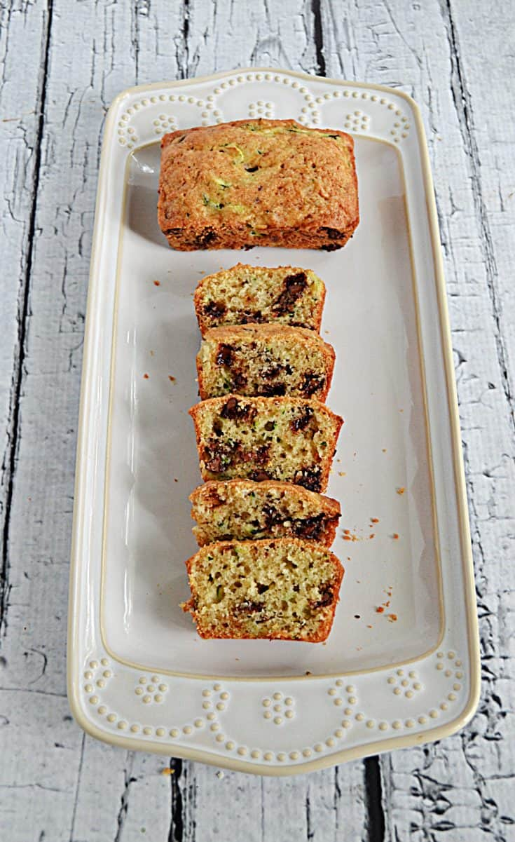 A mini chocolate chip zucchini loaf with one who loaf and one loaf sliced on a platter.