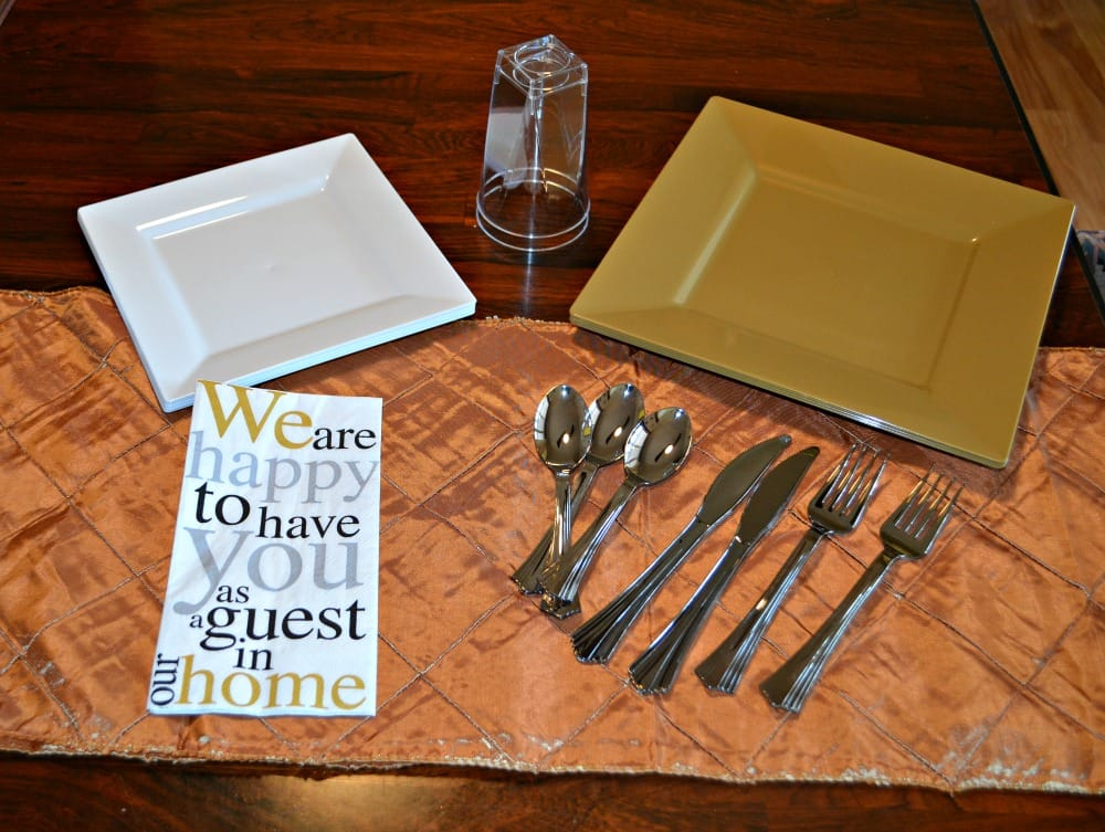 Awesome Gold Tablescape including plates, silverware, napkins, table runner, and cups from Smarty Had a Party