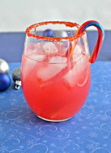 A stemless wineglass rimmed with red sugar, filled with pink liquid, with a candy cane swizzle stick, on a blue background.