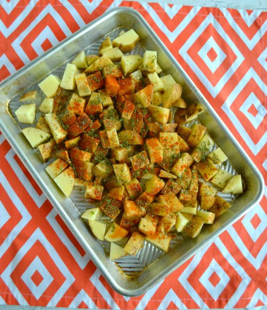 Raw potatoes with Greek seasonings on a sheet pan.