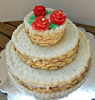 Triple Layer Wedding Cake decorated and topped with frosting roses.