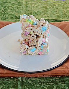 A plate stacked with Lucky Charms Treats on a gold background.