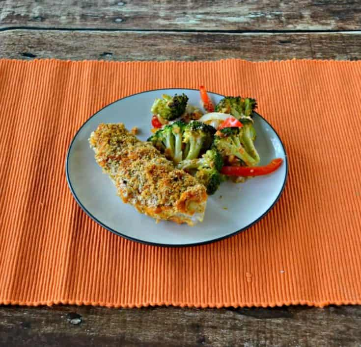 Delicious Hummus Crusted Chicken served with a side of roasted vegetables