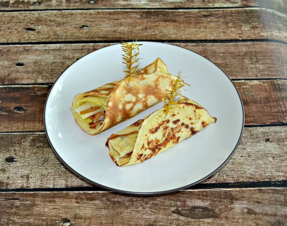 Bite of a piece of this Savory Breakfast crepe with egg, bacon, cheese, and pears for a delicious morning meal.