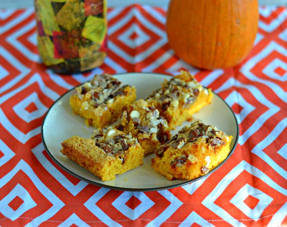 These Gooey Pumpkin Cookie Bars are topped with white chocolate, cinnamon chips, pecans, and covered with milk that turns to caramel when cooked.